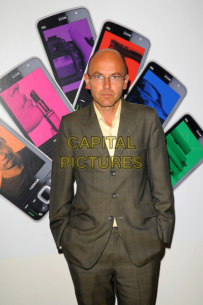 "WAYNE HEMINGWAY.The Nokia ""Capsule N96"" launch party, Century Club, Shaftesbury Avenue, London, England..September 22nd, 2008.half length grey gray suit glasses hands in pockets  .CAP/CAN.©Can Nguyen/Capital Pictures."