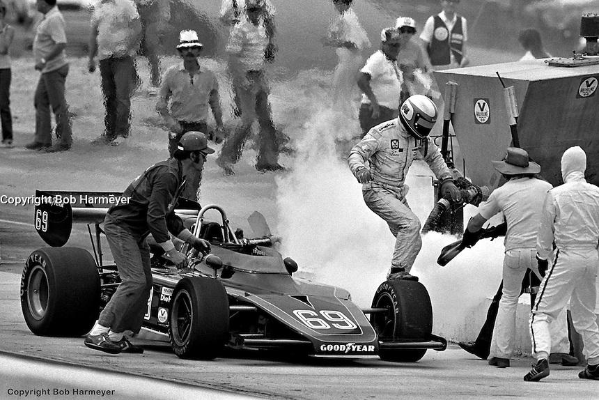 HAMPTON, GA - APRIL 22: Joe Saldana exits his Lightning 77/Offenhauser TC during a pit stop fire in the Gould Twin Dixie 125 event on April 22, 1979, at Atlanta International Raceway near Hampton, Georgia.