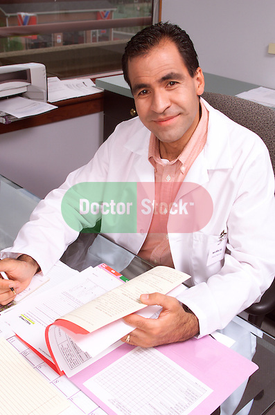 male doctor sitting at desk reviewing paperwork