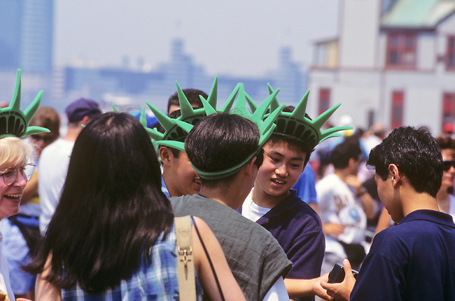 Tourists and visitors wearing Liberty hats in Battery Park. New York, New York.
