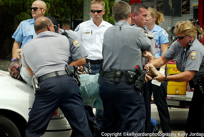 Daytona Beach Police officers along with fire/rescue personnel try to control a man who is in Police custody after wandering in and out of traffic at the intersection of Ridgewood and fairview Avenues with a knife and allegedly attacking a woman Tuesday afternoon, July 30, 2002.(Kelly Jordan)..**FOR REPORTER STORY**