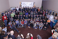 The entire field of 66 2013 Iditarod mushers pose for a group photo during a toast by the Millenium Alaska Hotel manager Carol Fraser. The photo was taken during the mandatory musher meeting at the Millenium hotel two days prior to the start of Iditarod 2013...Photo (C) Jeff Schultz/IditarodPhotos.com  Do not reproduce without permission.