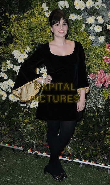 Gizzi Erskine.The John Lewis Beauty Hall launch party, John Lewis department store, Oxford St., London, England..May 8th, 2012.full length black dress tights velvet bell sleeves gold hand on hip  .CAP/CAN.©Can Nguyen/Capital Pictures.