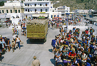 Backpacking tourists wait for cargo to be unloaded so that they can ferry to another Greek island.