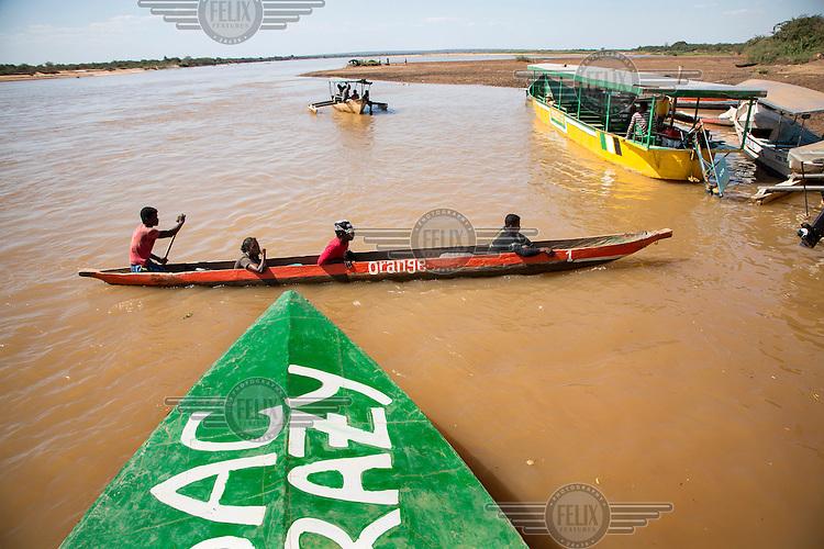 A canoe painted orange brings passengers across the Tsiribihina River