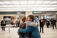 Passengers are greeted upon their arrival from Dubai after a 14-hour flight on Emirates flight 231, at the international terminal at Dulles International Airport in Dulles, Va., Monday, March16, 2020. Some people are taking the precaution of wearing face masks as they arrive to be greeted by family and or friends. Credit: Rod Lamkey / CNP/AdMedia