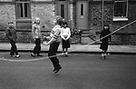 Saltaire, Yorkshire. England. Children playing together, skipping in the street. 1981