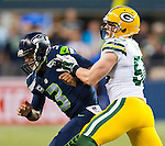 Seattle Seahawks quarterback Russell Wilson (3) is shoved by Green Bay Packers linebacker A. J. Hawk (50)  in the NFL Kickoff held at CenturyLink Field September 4, 2014 in Seattle. Casey was flagged on the play. Wilson completed 19 passes for 191 yards, rushed for 29 yards as The Seahawks beat the Packers 36-16.   ©2014.  Jim Bryant Photo. ALL RIGHTS RESERVED.