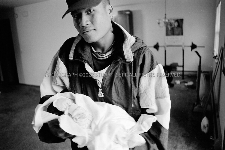 4/1994--Chicago, USA..Bobby and his new born daughter...All photographs ©2007 Stuart Isett.All rights reserved.This image may not be reproduced without expressed written permission from Stuart Isett.
