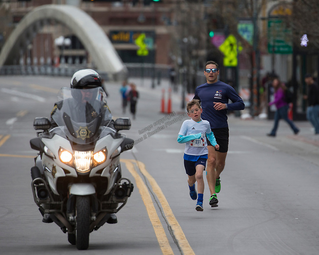 Jr 1 Mile winner Rhys Ferrito is escorted to the finish line during the 6th Annual Reno 5000 Downtown River Run on Saturday, April 6, 2019.