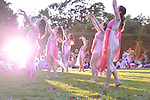 Old Westbury, New York, U.S. 22nd June 2013. At the Midsummer Night event at Old Westbury Gardens, a visitor's camera flash lights up dancers in Lori Belilove & The Isadora Duncan Dance Company, and The Beliloveables, as they perform the final dance of the night, in the South Terrace in front of the mansion of the historic Long Island Gold Coast estate.