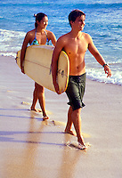 A teenaged boy and girl carry a surfboard in tandem along the shoreline at Waikiki Beach.