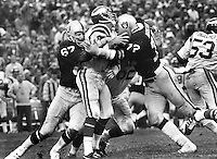 Oakland Raiders Pat Toomay and John Matuszak put the crush on Minnesota QB Tom Kramer. (1977 photo by Ron Riesterer)