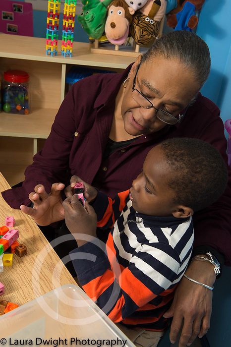 Education Preschool 4 year olds female teacher working with boy playing with connecting plastic cubes