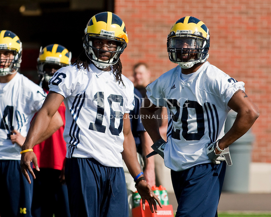 Michigan quarterback Denard Robinson (16) and running back Michael Shaw (20) stand watching teammates run through drills on the first day of spring football practices, Tuesday, March 16, 2010, in Ann Arbor, Mich. (AP Photo/Tony Ding)