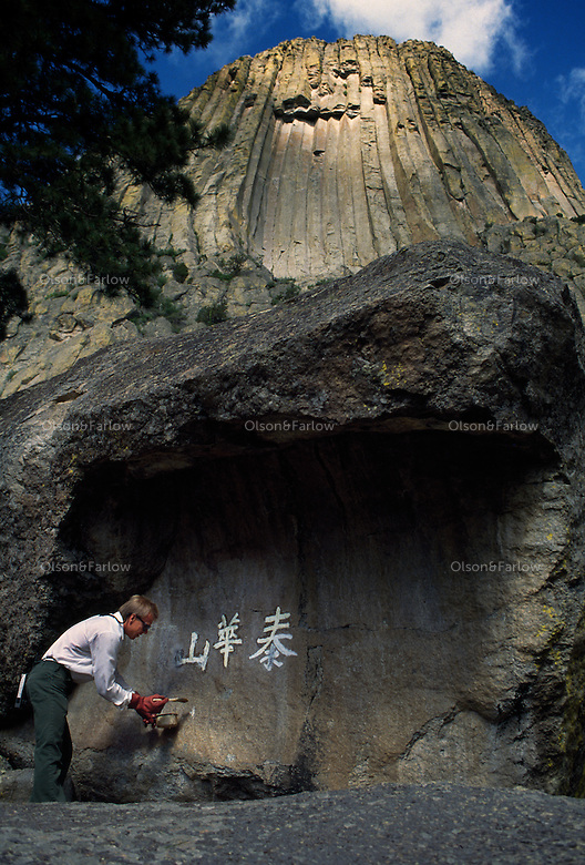 A park employee cleans Japanese graffiti off of Devil's Tower, an ancient volcano plug  or monolithic igneous intrusion that is more than 1200 feet high. It was featured in the Hollywood movie Closer Encounters of the Third Kind in 1977.