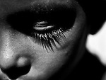 A face of a solemn child with large big eyelashes and its shadow on his cheek. Photograph © Santosh Verma