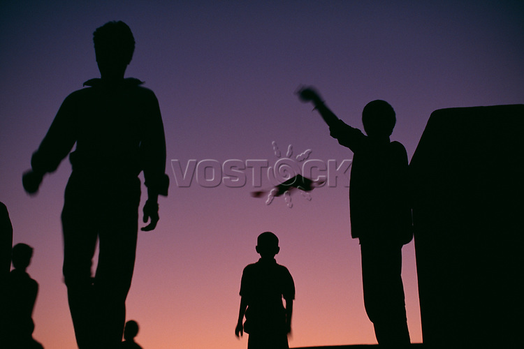 Silhouettes of people flying kites