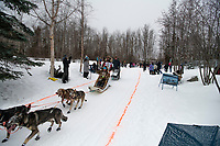 Peter Kaiser and team run past spectators on the bike/ski trail near University Lake with an Iditarider in the basket and a handler during the Anchorage, Alaska ceremonial start on Saturday, March 7 during the 2020 Iditarod race. Photo © 2020 by Ed Bennett/Bennett Images LLC