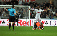 Pictured: Kemy Agustien of Swansea stands over Adel Taarabt of QPR while match referee Lee Probert (L) gives a foul in favour of the latter. Tuesday 27 December 2011<br /> Re: Premier League football Swansea City FC v Queens Park Rangers at the Liberty Stadium, south Wales.