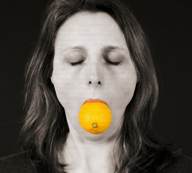 A middle aged woman with shoulder length brown hair with an orange wedged in her mouth