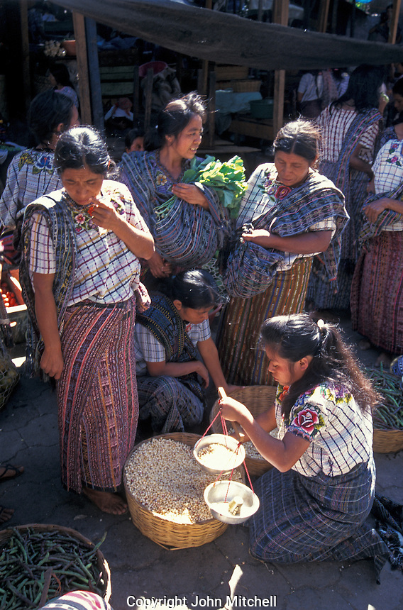 Maya woman wieighing dried corn for a customer in the market in Santiago Atitlan, Guatemala