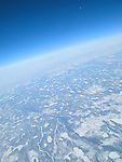 Aerial view form airplane of frozen, snow covered earth.