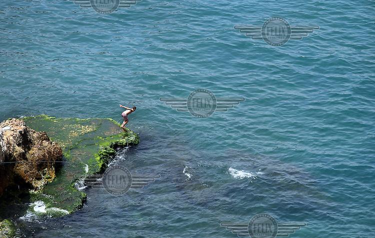 A man dives off Beirut's popular seafront promenade, Corniche Beirut.