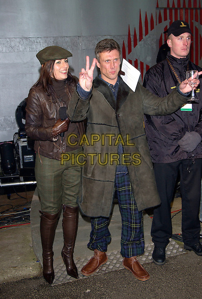 DAVINA McCALL & BEZ.Celebrity Big Brother 3 Grand Final, Elstree Studios, Hertfordshire..January 23rd, 2005.full length, brown leather jacket, green trousers tucked into brown boots, plaid trousers, gesture, v sign, peace sign.www.capitalpictures.com.sales@capitalpictures.com.©Capital Pictures