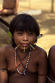 Paapiu, Roraima State, Brazil. Yanomami Indian girl with pierced mouth adorned with split bamboo sticks, feather ear decorations