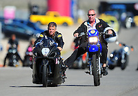 Oct. 29, 2011; Las Vegas, NV, USA: NHRA pro stock motorcycle rider Jerry Savoie (left) with a crew member during qualifying for the Big O Tires Nationals at The Strip at Las Vegas Motor Speedway. Mandatory Credit: Mark J. Rebilas-
