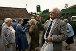 'WINE IN ENGLAND, SOMERSET', MRS GILLISPIE TAKES A PARTY OF TOURISTS AROUND THE VINEYARD, HERE ONE ELDERLY MAN HOLDS A BOTTLE UP TO THE LIGHT TO CHECK THE COLOUR, 1989