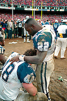 "SAN FRANCISCO, CA - Running back Emmitt Smith of the Dallas Cowboys consoles teammate Daryl ""Moose"" Johnston on the bench during the NFC Championship Game against the San Francisco 49ers at Candlestick Park in San Francisco, California in 1995. Photo by Brad Mangin"