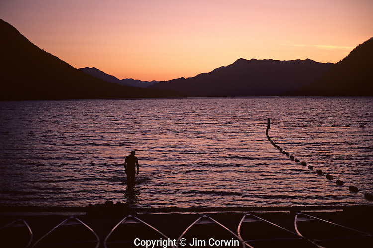 Canoes lined up in a row along the shoreline of Lake Wenatchee at sunset with silhouetted man walking out of the lake Eastern Washington State USA