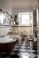 The walls of a guest bathroom are decorated with family photographs