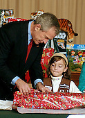 Washington, D.C. - December 22, 2006 -- United States President George W. Bush helps an unidentified Brownie Scout wrap a Christmas gift destined for injured soldiers and their families who are staying at the Mologne House at the Walter Reed Army Medical Center in Washington, D.C. on Friday, December 22, 2006.<br /> Credit: Ron Sachs - Pool via CNP