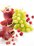 Pomegranate seeds, Cranberries, Apple slice, Green Grapes on white surface