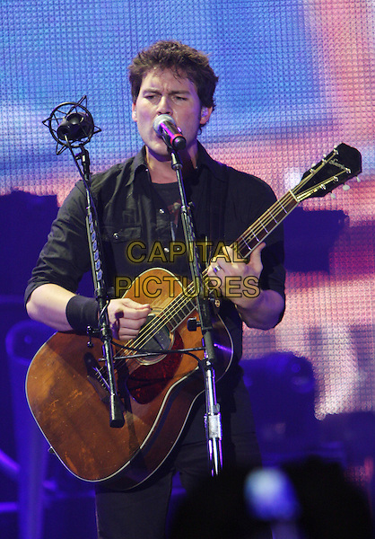 NICKELBACK  - Ryan Peake.Perform live in concert at Wembley Arena, London, England, UK,.19th January 2010..music gig band tour on stage playing performing guitar group half length singing microphone black shirt .CAP/MAR.© Martin Harris/Capital Pictures.