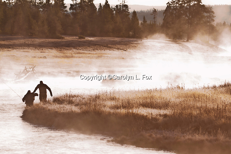 A man helps another fisherman into the water on the Madison River in Yellowstone.