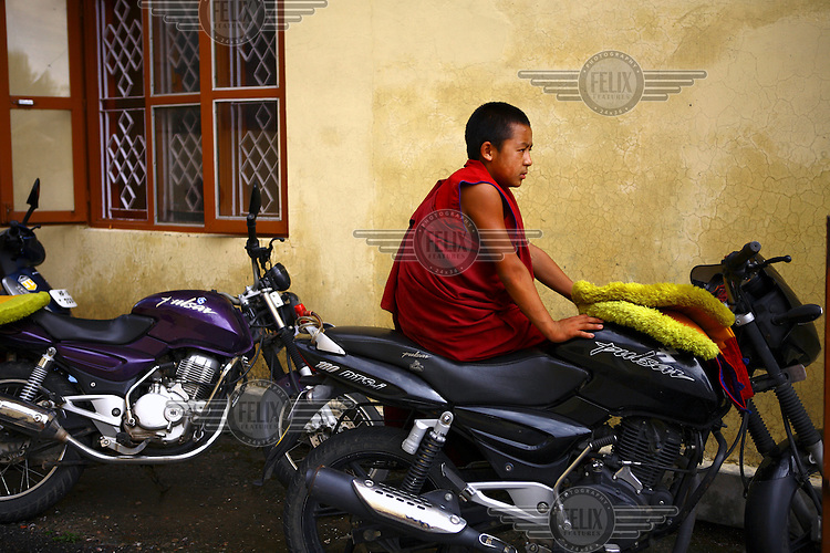 A young monk from the Gyuto Tantric Monastic University sits on a parked motorcycle.