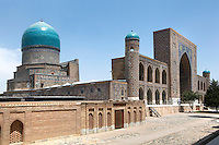 General view of Tillyah-Kori Madrasah, 1646-60, Registan, Samarkand, Uzbekistan, pictured on July 15, 2010, in the morning. The Tillyah-Kori (gilded) Madrasah is part of the Registan Ensemble, surrounding a magnificent square. Commissioned by Yalangtush Bakhadur it is not only a school but also the grand mosque whose lavishly gilded main hall in Kundal style justifies the name. The 75 metre main facade is two-storied with corner turrets and  decorated in brilliant mosaic. Around the courtyard are the dormitory cells.  The dome was only completed during the 20th century Soviet restoration. Samarkand, a city on the Silk Road, founded as Afrosiab in the 7th century BC, is a meeting point for the world's cultures. Its most important development was in the Timurid period, 14th to 15th centuries. Picture by Manuel Cohen.
