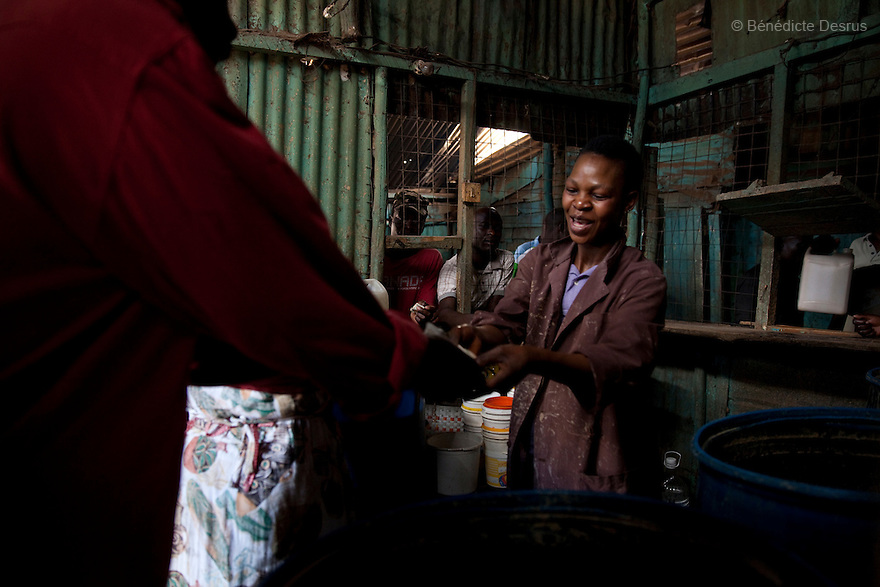 Alice Mutuwa working at the Madiaba Busaa Club in a Nairobi slum on April 7, 2013. Alice has been selling Busaa, a traditional fermented beer, for more than 10 years at the Madiaba Busaa Club. Busaa is made by crudely fermenting maize, millet, sorghum or molasses. At Kshs 35 per liter it is much cheaper than a Kshs120 half-liter bottle of commercial beer. The local brew was legalised in 2010 and since then busaa clubs have become increasingly popular. Drinking is on the rise in Kenya, especially among young people. Photo by Benedicte Desrus