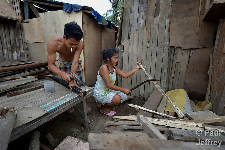After the passage of Typhoon Bopha, Crispin Sabelia (left) and Adelle Sabelia, both displaced by the storm in Iligan, on the southern Philippines island of Mindanao, recycle lumber that was left behind by the receding waters. The ACT Alliance assisted members of this community with emergency food and other supplies.