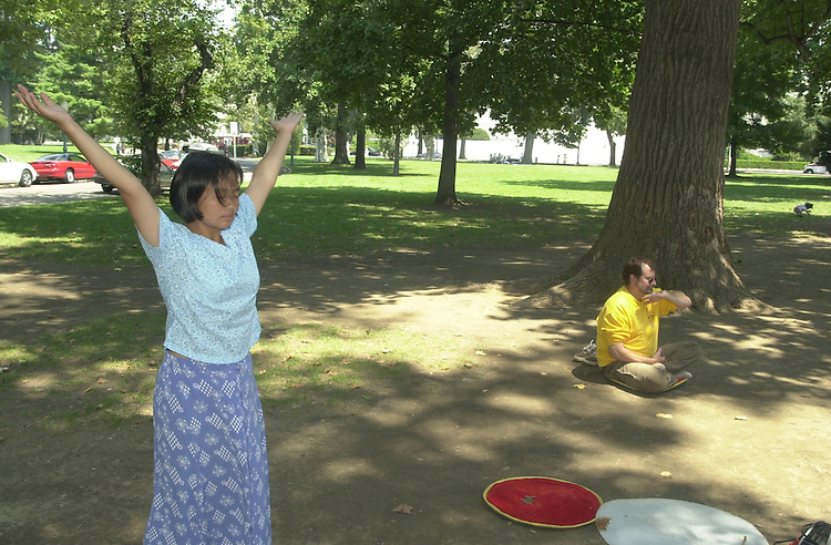 1feature080701 -- Tiny Tang, of Fairfax, VA. and Robert Nappi, of Alexandria, VA. practice Falun Dafa on a sweltering Tuesday afternoon on the east lawn of the Capital.
