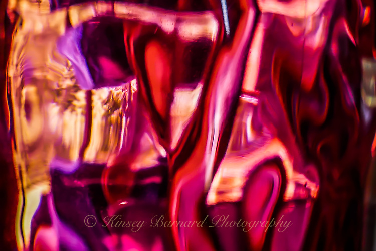 Light reflected through a rose colored glass of water.