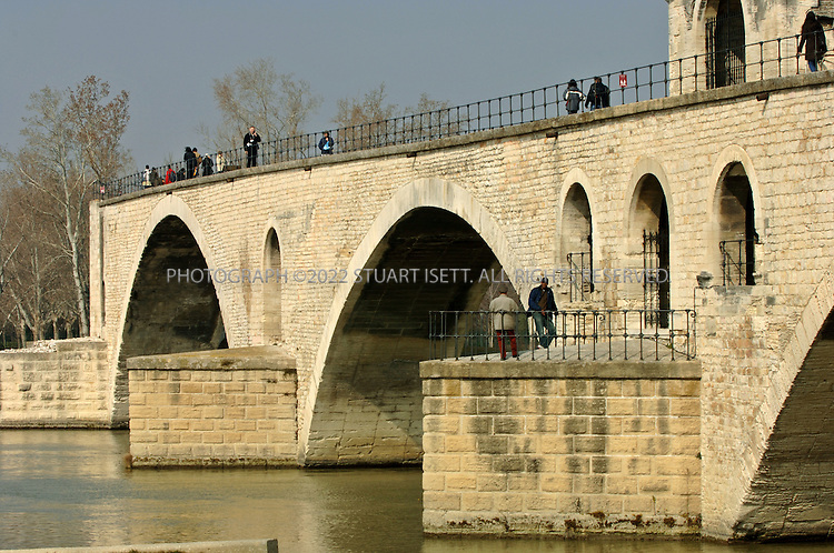 2/25/2006--Avignon, France..The bridge of Saint-Benezet, also called the Pont d?Avignon, at rue Ferruce. Built in the late 1100s, most of the bridge was destroyed by the raging flood waters of the Rhone river, leaving it with four remaining arches out of its original twenty-two. Legend has it that the lyrics, claiming the people danced on (sur) the bridge, were altered over time, and that they actually danced under (sous) the bridge. Entrance costs 3.5 euros and comes with a free audio guide (available in English)..Photograph By Stuart Isett.All photographs ©2005 Stuart Isett.All rights reserved.