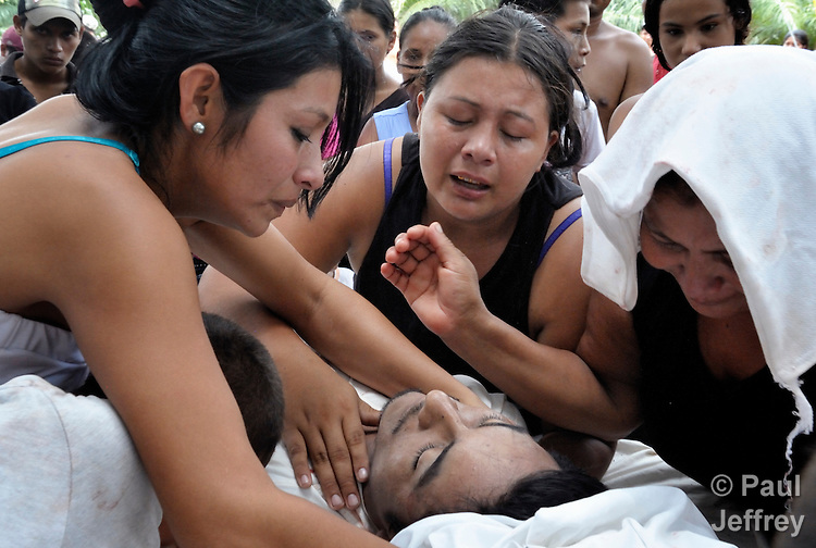 Relatives mourn over the body of Carlos Martinez, a 23-year old farmworker who was shot to death on October 2 on the La Lempira Cooperative outside Tocoa, Honduras. Left to right is sister Marlin Martinez, sister Karin Martinez, and mother Victoria Martinez. Carlos Martinez and other members of the cooperative are among thousands of Honduran activists who have seized plantations they claim were stolen from them by wealthy Honduras businessmen. The Honduran security forces have militarized the area, and killings of peasant leaders have become common. Many of the cooperatives were started with assistance from Catholic priests and lay pastors in the region, and some Catholic leaders remain close supporters of the peasant movement. A sister of Martinez claimed he was killed by a security guard from a nearby plantation belonging to Miguel Facusse, the wealthiest of Honduran landowners.