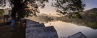 Panorama of Kandy Lake and people walking at the Clouds Wall (Walakulu Wall) at sunrise, Kandy, Central Province, Sri Lanka, Asia. This is a panorama of Kandy Lake, with people walking along the Clouds Wall (Walakulu Wall) at sunrise in Kandy, Central Province of Sri Lanka, Asia. Kandy is the second largest city in Sri Lanka, and is home to beautiful Kandy Lake and Clouds Walls (Walakulu Wall), a great place to visit for a walk at sunrise. The Sacred City of Kandy is one of eight UNESCO World Heritage Sites in Sri Lanka.