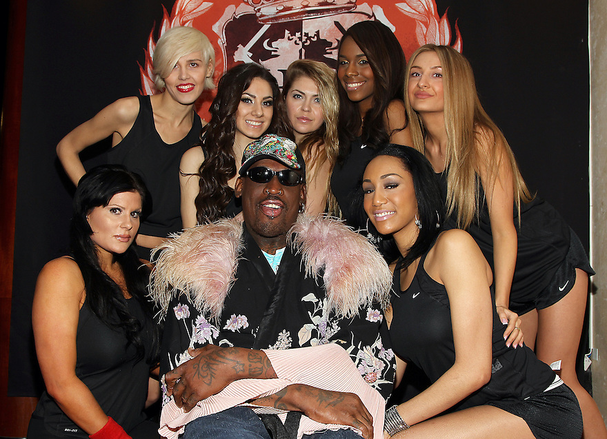 Players Polina, Candice, Kristina, Tanisha, Inga from left to right standing, seated players Adrienne and Layla with coach Dennis Rodman center, pose for a photo at the press conference for HQ's strippers basketball team in New York, on Thursday, Mar. 01, 2012. (AP Photo/ Donald Traill)