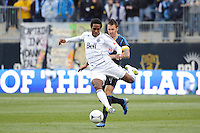 Atiba Harris (9) of the Vancouver Whitecaps plays the ball under pressure from Danny Califf (4) of the Philadelphia Union during a Major League Soccer (MLS) match at PPL Park in Chester, PA, on March 31, 2012.